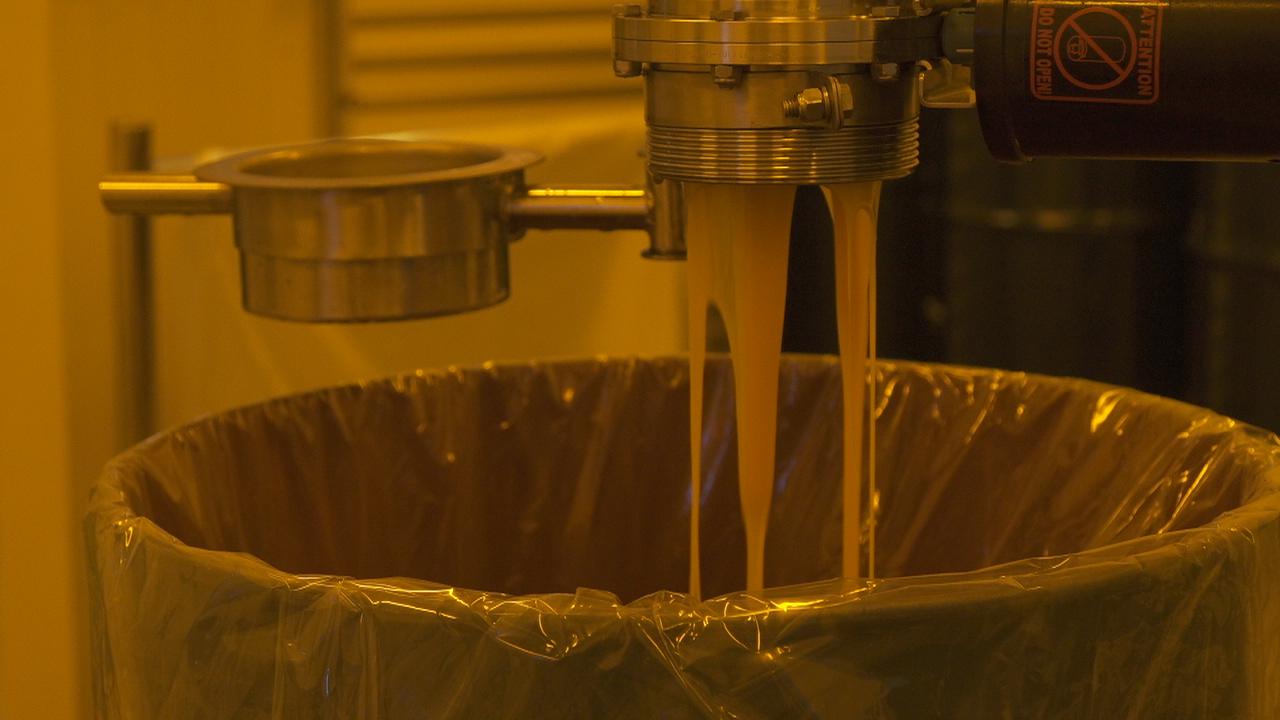 Orangensaftkonzentrat wird in einer Fabrik gepresst und aufgefangen.