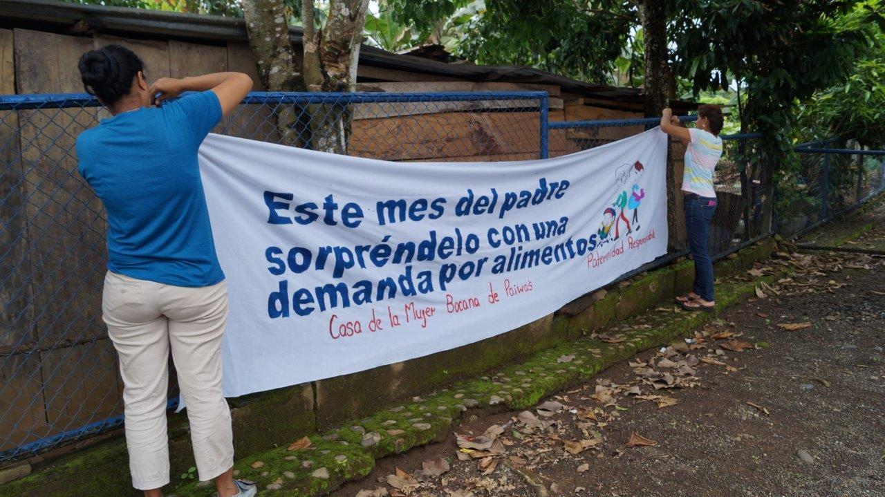 Frauen der Casa de la Mujer hängen ein Transparent auf, um Frauen zu ermutigen Alimentezahlungen einzuklagen.