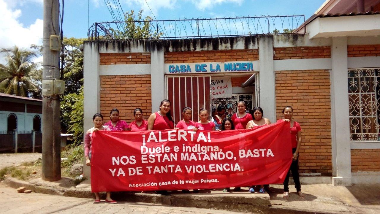Frauen der Casa de la Mujer halten ein Transparent gegen Gewalt an Frauen