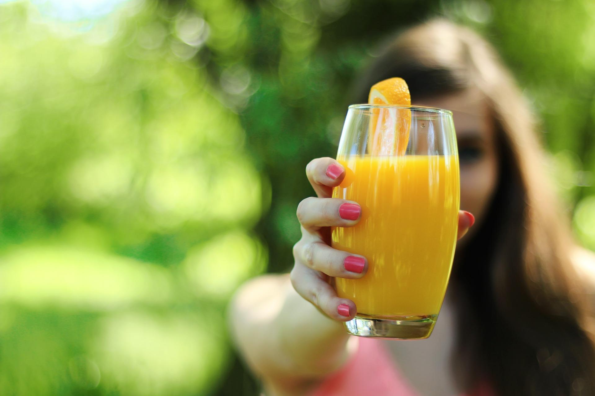 Frau hält Glas mit Orangensaft in Kamera
