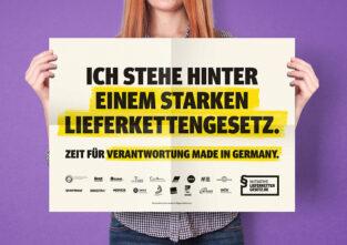 """teilweise sichtbare Person (ohne Kopf und Füße) hält hoch: Weißes Din A2 Poster mit schwarzer Blockschrift, teilweise geld hinterlegt: """"Ich stehe hinter einem starken Lieferkettengesetz. Zeit für Verantwortung Made in Germany."""" Darunter sind das Logo der Initiative Lieferkettengesetz sowie 18 Logos von tragenden NGOs u.a. der CIR e.V."""