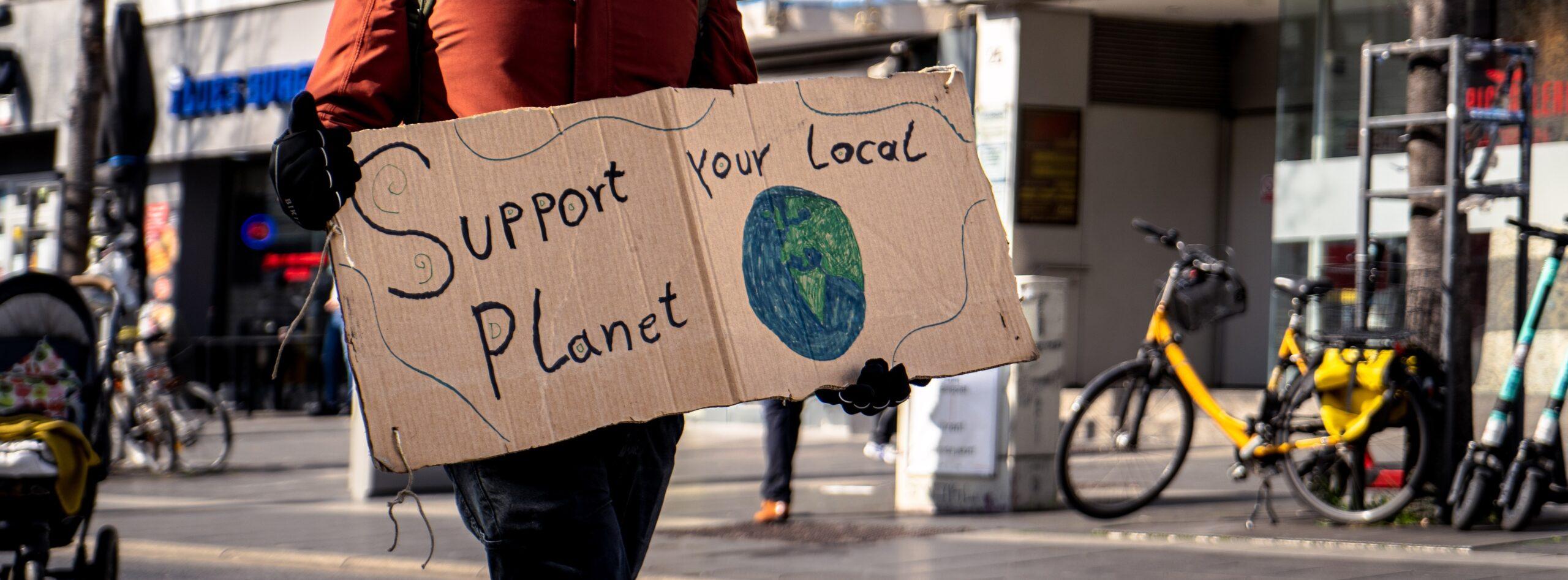 Demo-Schild: Support your local planet - Unterstütze deinen Planeten lokal