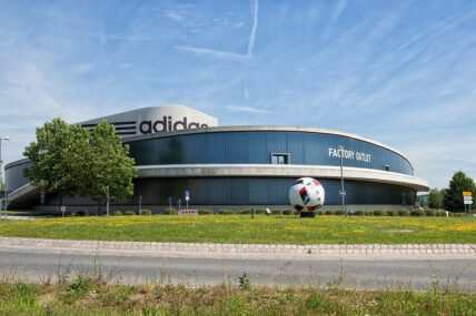 AdidasHauptquartier in Herzogenaurach mit großem Fußball-Monument davor auf einer Wiese