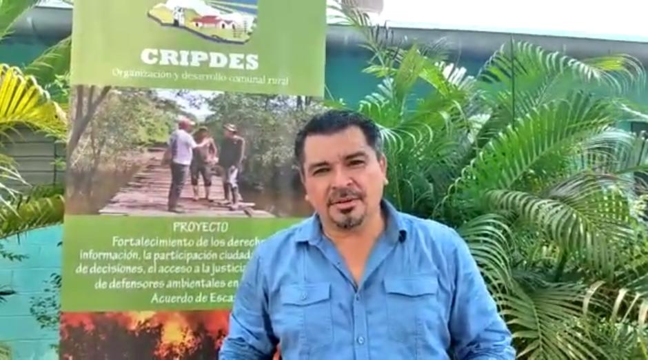 Der Leiter von CIR Partnerorganisation CRIPDES steht draußen vor Palmen und einem CRIPDES-Banner und sprcht in die Kamera